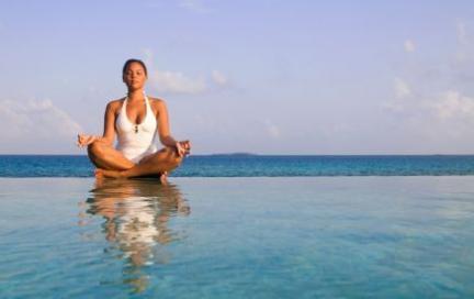 woman meditates in ocean