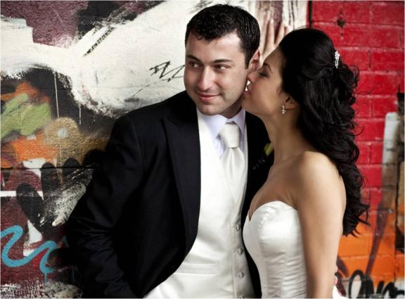 bride in vera wang strapless wedding dress whispers into the ear of her groom with an urban NYC background