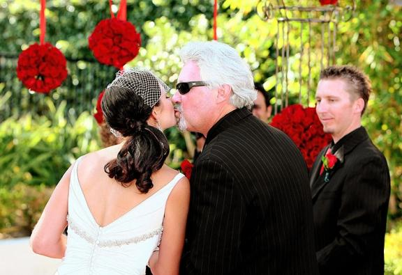 Vintage chic bride kisses father at end of ceremony aisle