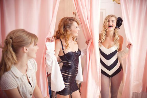 Bride and bridesmaids try on retro wedding lingerie at bachelorette party