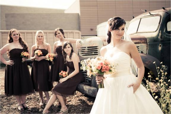 Bride in classic ball gown wedding dress poses with bridesmaids, wearing chocolate brown strapless dresses