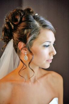 Classic bridal updo parted on the side, with curls piled high towards the back of the head, tendrils framing bride's face