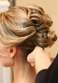 Sleek, modern wedding hairstyle updo with sideswept bangs and loose curls pinned into an updo