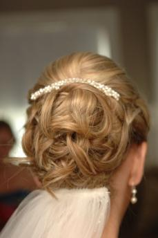 Blonde bride wears classic wedding hairstyle- sleek curly up-do pulled all back, accented with pearl hair barrette and tulle bridal veil