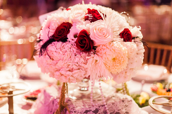 epic wedding in Los Angeles California weddings red rose with feathers pearls centerpiece