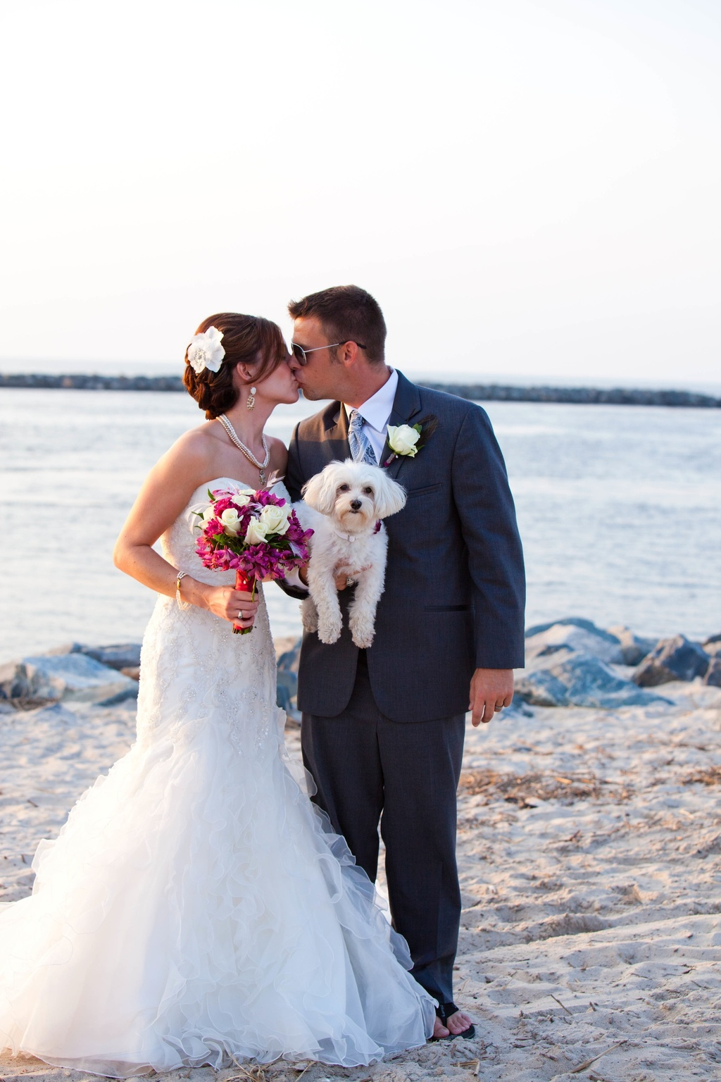 Beach-wedding-in-delaware-bride-groom-kiss-while-holding-dog.full