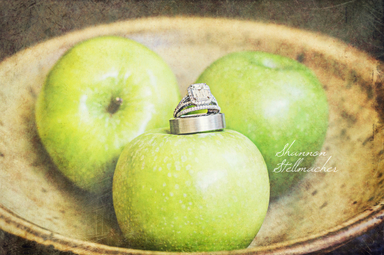 Engagement Ring and Wedding Bands Photo atop green apples
