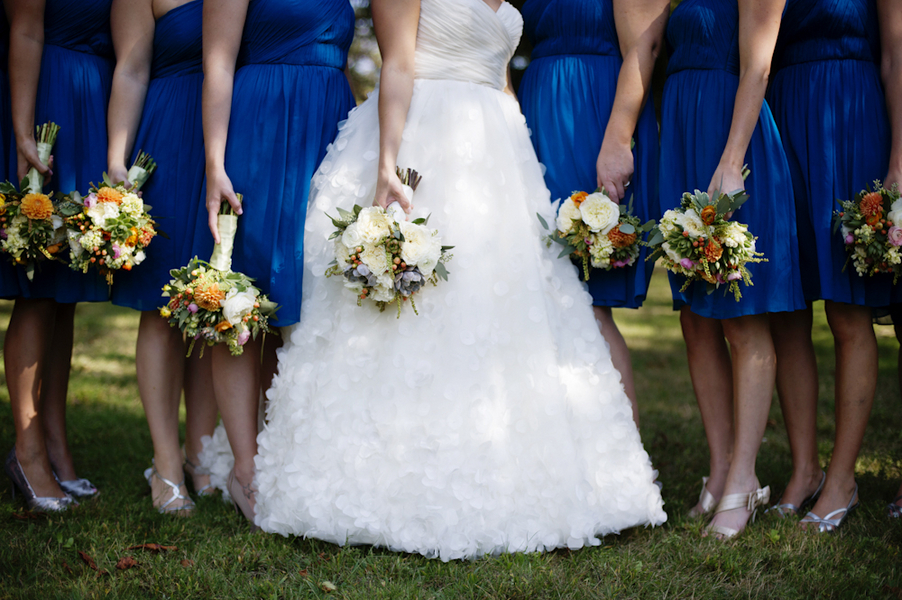 Bride-poses-with-bridesmaids-in-blue-showing-off-bouquets.full