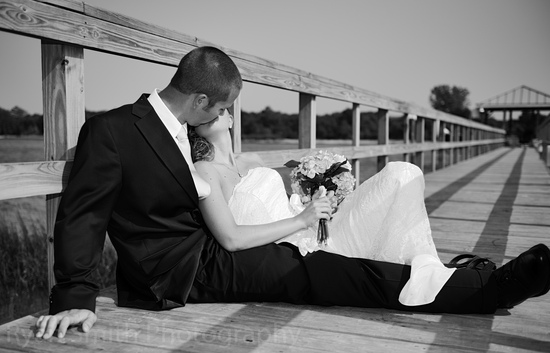 Bride and Groom laying on pier in gritty black and_4604515696_o