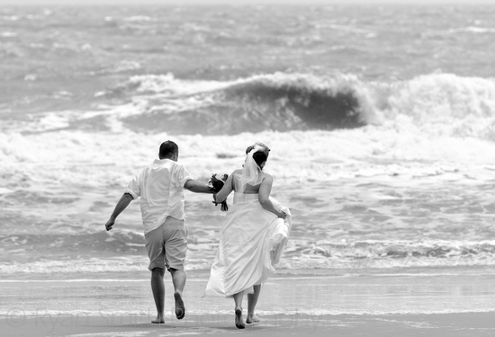 Bride and groom running toward the waves_5625935256_o