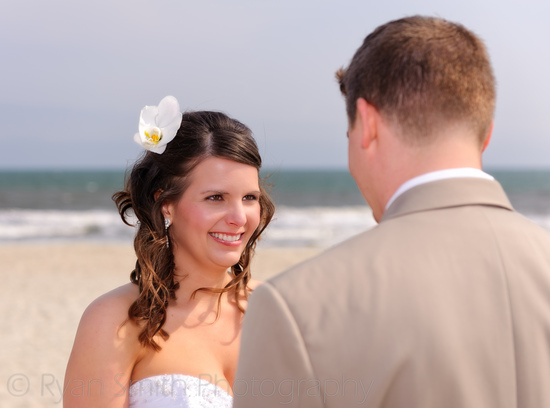 Bride smiling at groom during ceremony - Ocean Isle Beach_5617117600_o
