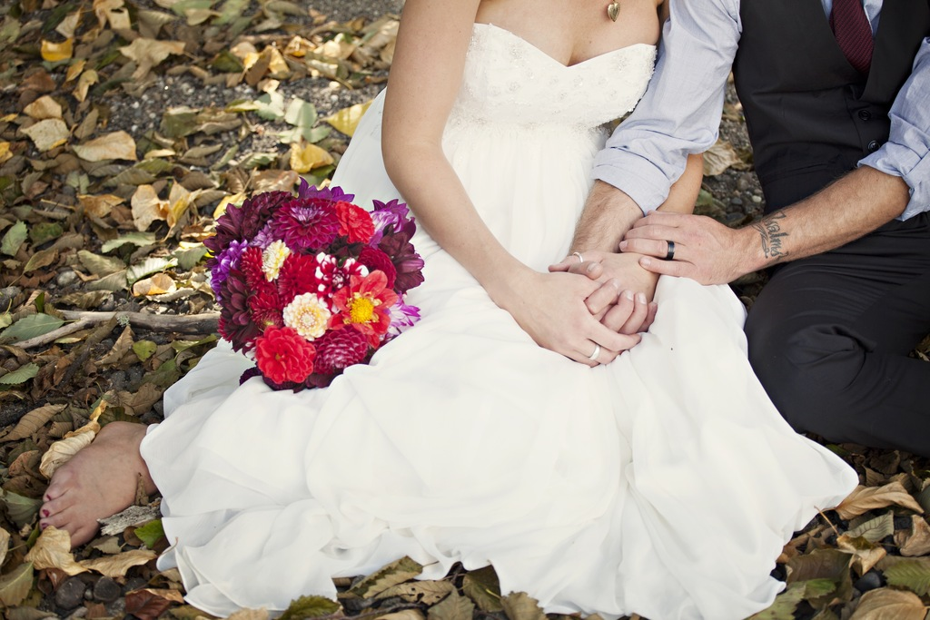 Fall Bride and Groom Pose Outside with Red Bridal Bouquet