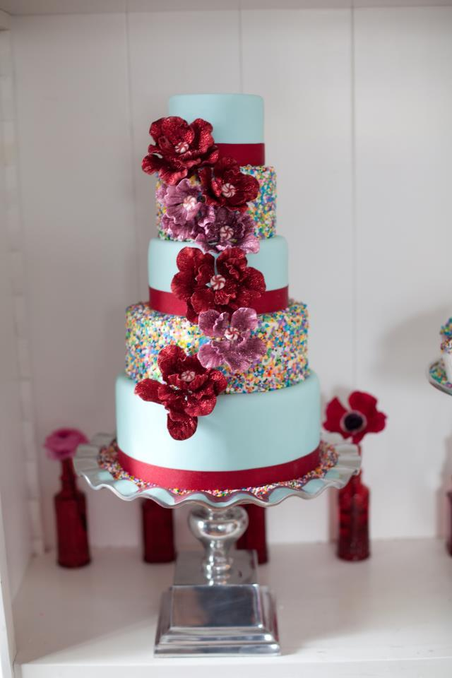 Whimsical-wedding-cake-with-rainbow-sprinkles-red-blooms.full