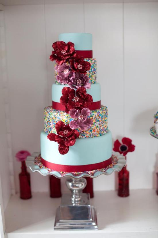 photo of Whimsical Wedding Cake with Rainbow Sprinkles Red Blooms