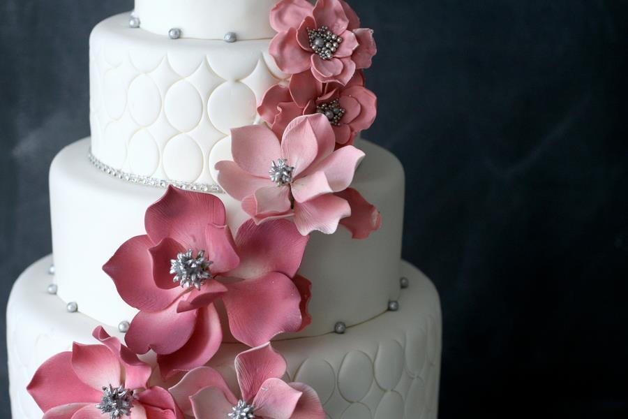 Elegant-white-wedding-cake-with-light-pink-blooms-silver-beads.full
