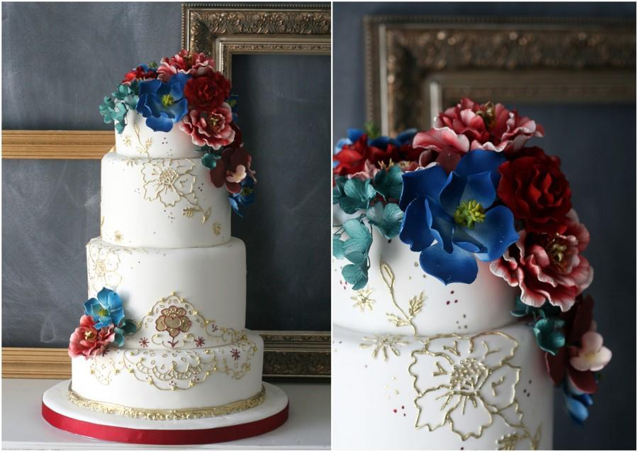 Elegant-white-and-gold-wedding-cake-with-jewel-tone-blooms.full