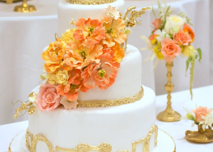 White-and-gold-wedding-cake-with-bright-peach-orange-yellow-sugar-flowers.full