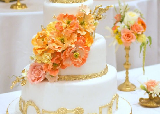White and Gold Wedding Cake with Bright Peach Orange Yellow Sugar Flowers