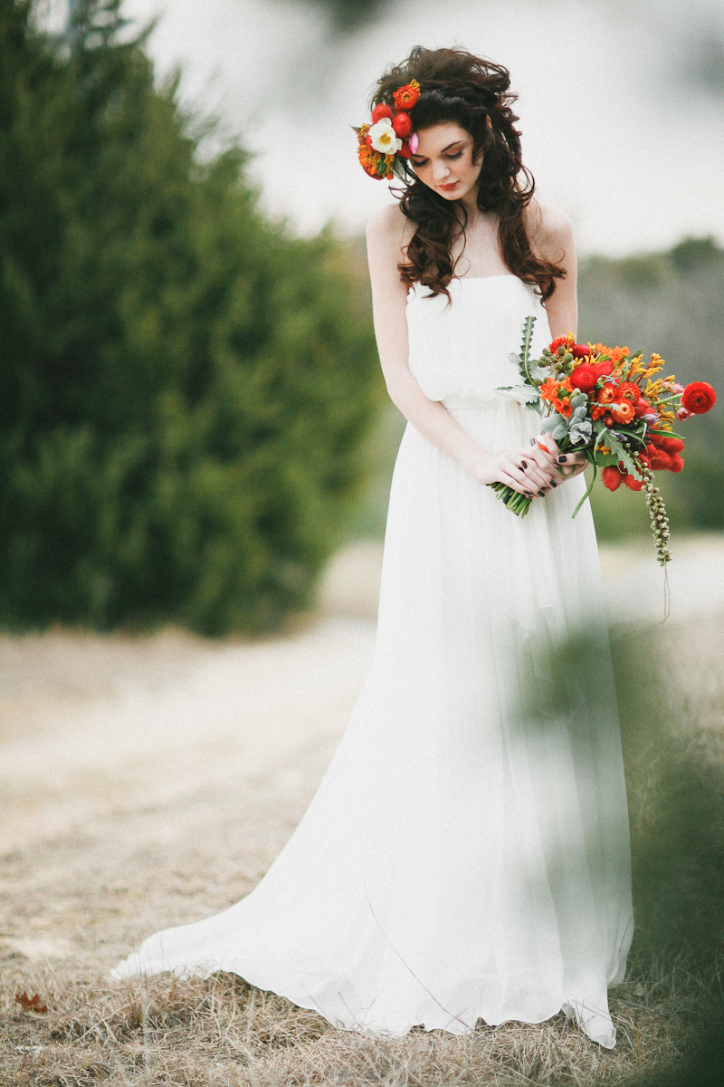 Romantic-fall-bride-poses-outside-with-rich-red-bouquet.full