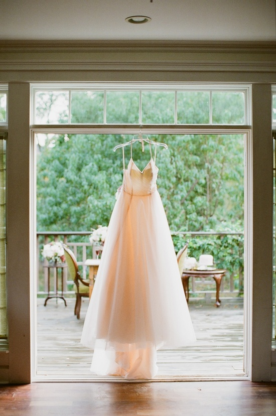 Brides Ivory Wedding Dress Hangs in Window