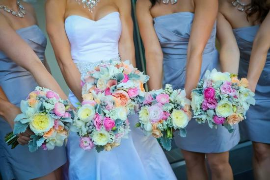 photo of Bridesmaids in Gray Show Off Romantic Bouquets