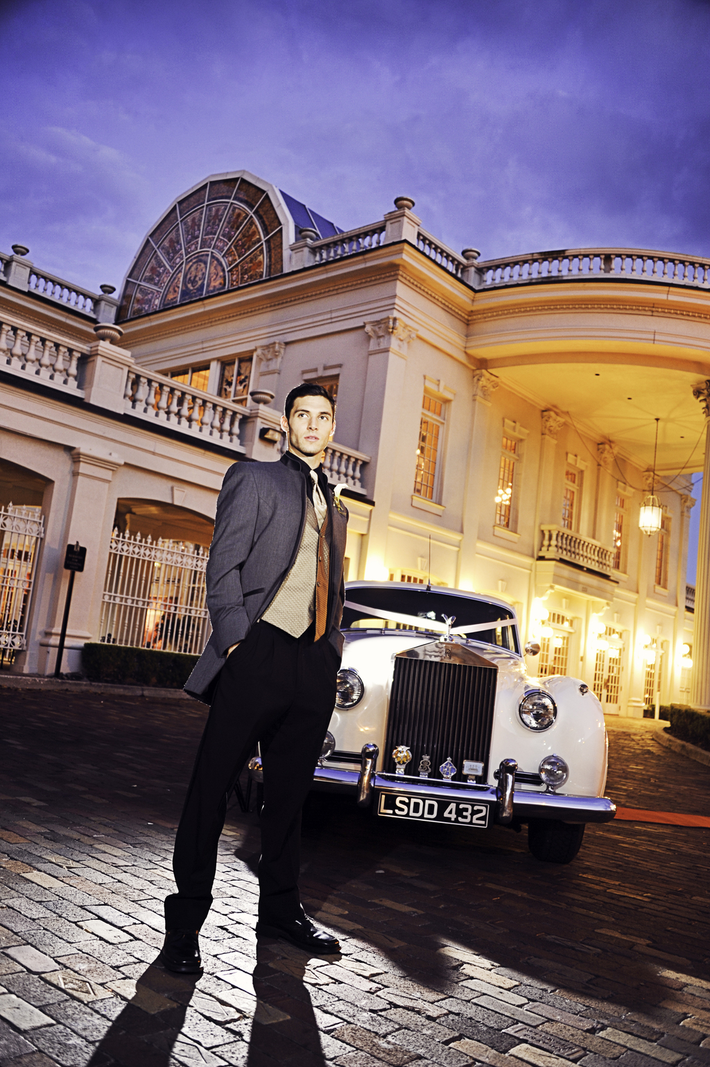 Opulent-wedding-venue-vintage-groom-poses-with-rolls-royce.full