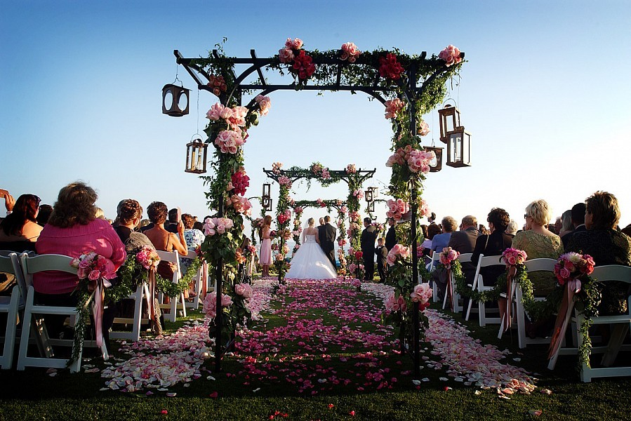 Outdoor wedding ceremony in Laguna Beach with pink flowers and petals decorating the aisle