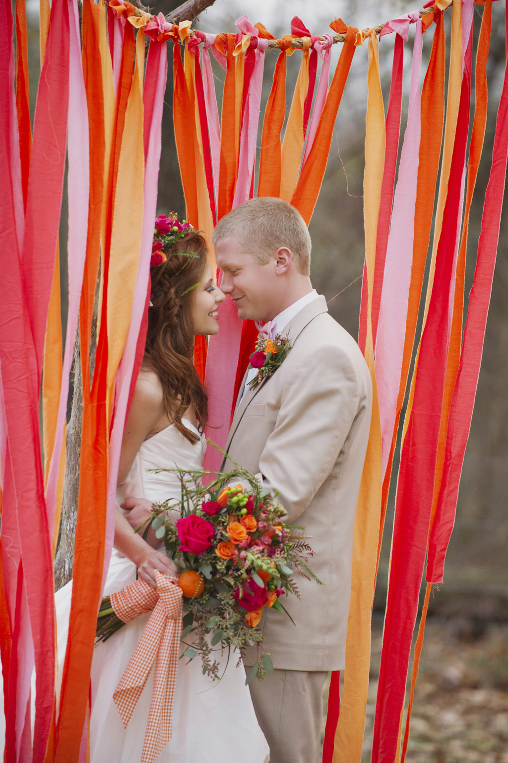 Bride-and-groom-embrace-beneath-bright-ceremony-backdrop.full