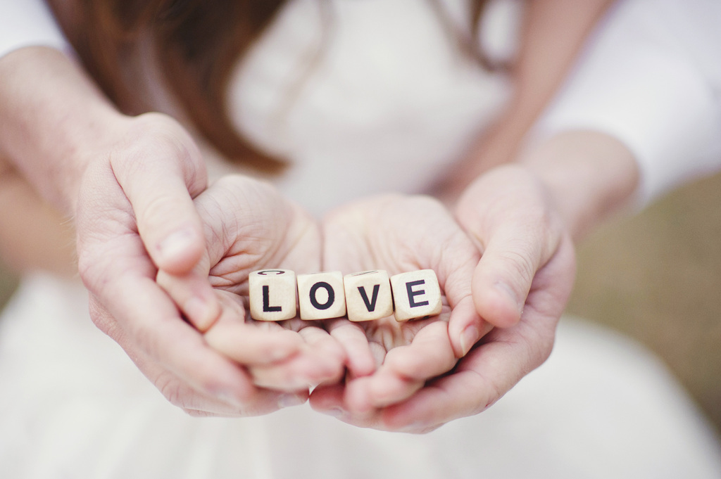 Bride and Groom Hold Dice Spelling Love