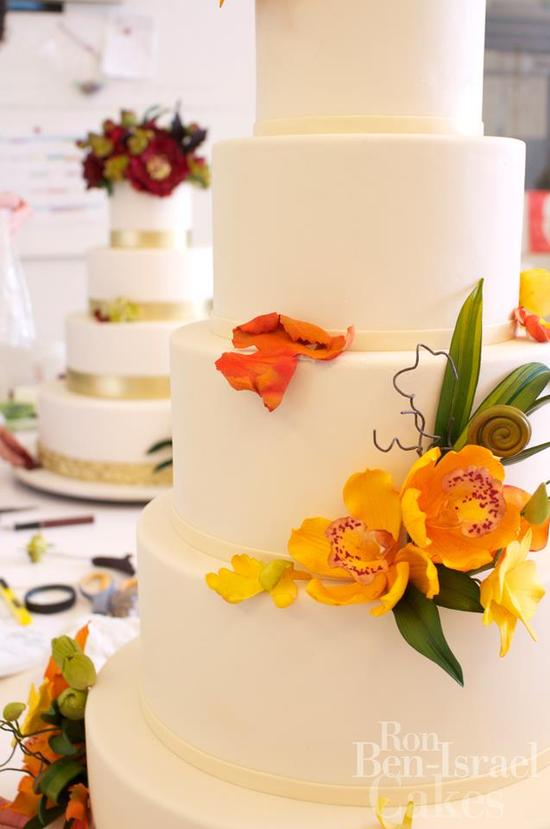 photo of ivory-wedding-cake-with-orange-fllowers