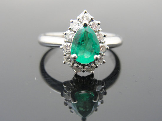 Emerald engagement ring with diamond halo