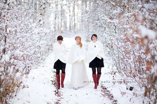 Winter bride walks through snow with bridesmaids