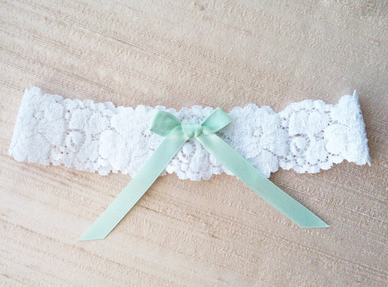 Delicate white lace wedding garter with mint green bow