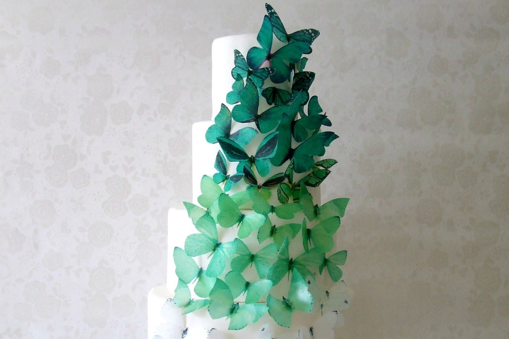 White wedding cake adorned with green butterflies
