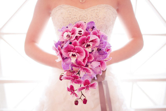 Exotic cascading wedding bouquet of purple pink orchids
