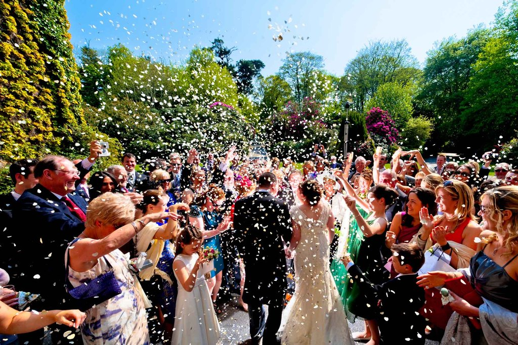 Bride and groom showered with petals after wedding ceremony