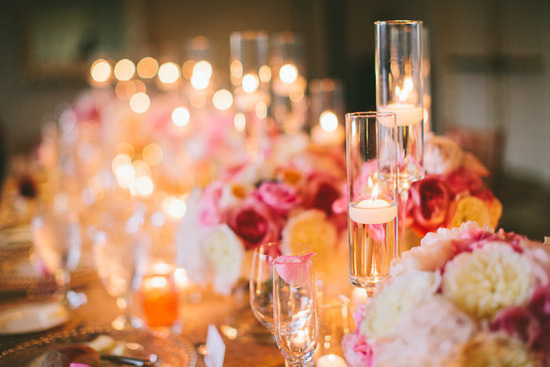 Romantic wedding reception table with high low candle accents