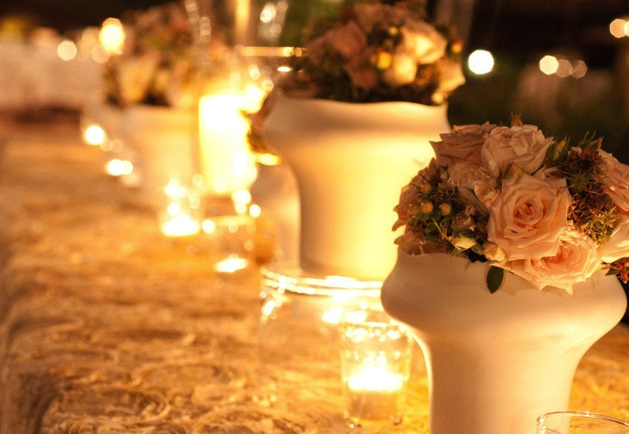 Potted centerpieces and flickering candles at outdoor wedding reception