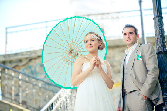 Vintage bride poses with groom and turquoise umbrella