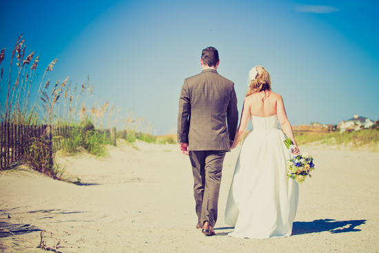 Beach bride and groom walk hand in hand