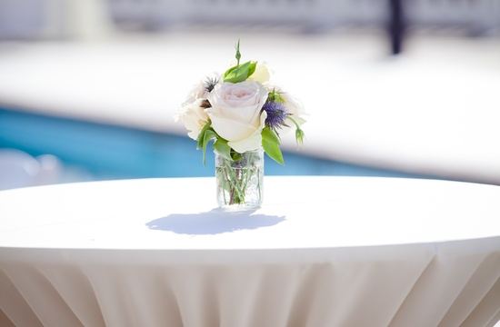 Simple wedding centerpiece atop highboy table