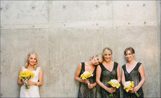 bride and bridesmaids pose together, holding yellow bouquets