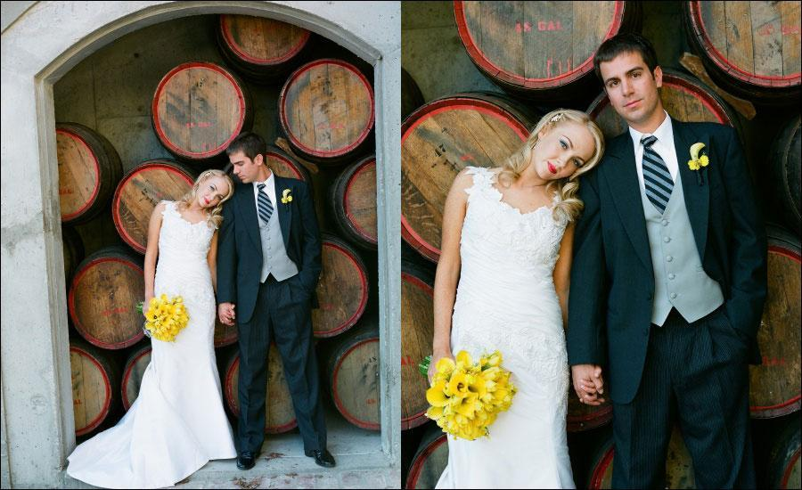 bride and groom stand together in front of winery barrels
