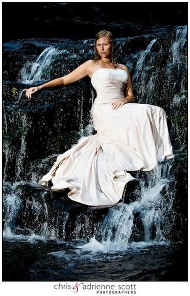 Bride in white wedding dress poses, poised on a waterfall