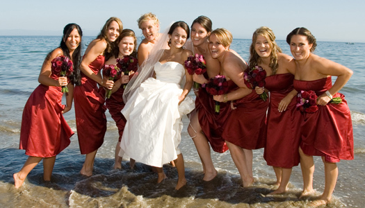 Smiling bride in white wedding dress surrounded by bridesmaids in red dresses