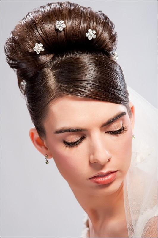 Stick pin hair crystals with white veil tacked onto back of bun for wedding day hair