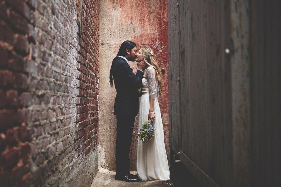 Bride-and-groom-kiss-in-urban-rustic-wedding-venue.full
