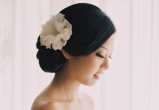 Classic chignon wedding hair with white flower