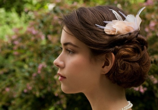 Elegantly twisted wedding hairstyle with fascinator
