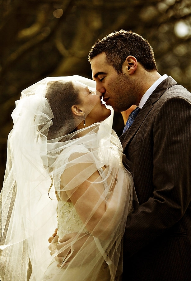 in white wedding dress and veil is held by groom, kiss lovingly
